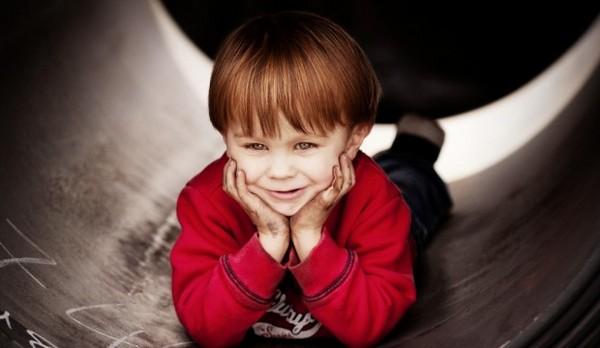 Lausbube Jamie liegt beim Fotokurs im Stahlcoil und lächelt durch seine schmutzigen Hände