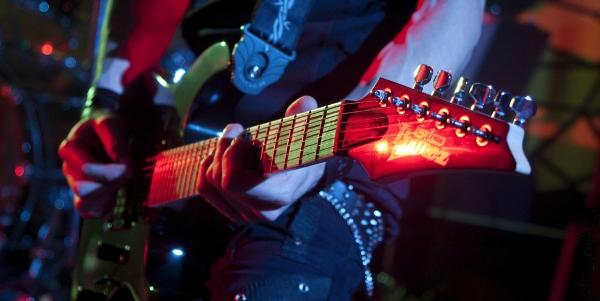 Foto des Instruments eines Gitarristen bei einem Konzert. Die Kamera blind zu beherrschen ist die Basis für gute Konzertfotografie