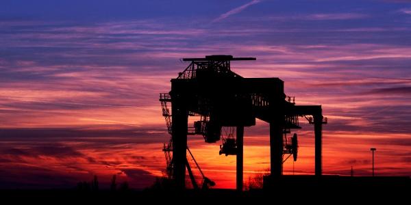 Container-Kranbrücke als Schattenriss im Sonnenuntergang
