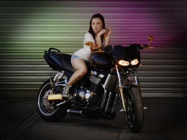 Das Lottchen auf dem Motorrad mit bunten Blitzen auf dem Rolltor im Hintergrund. Die Kamera beherrschen muss man auch bei jeder Form der Fotografie mit Blitz