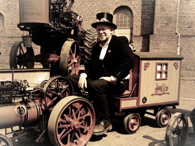 Steampunk auf Zeche Hannover. Mann in Frack und Zylinder steuert eine Miniatur-Dampfmaschine