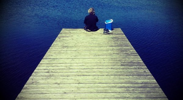 """Photowalk und Fotokurs """"Kleine Fotoschule"""", Person sitzt am Ende des Stegs"""