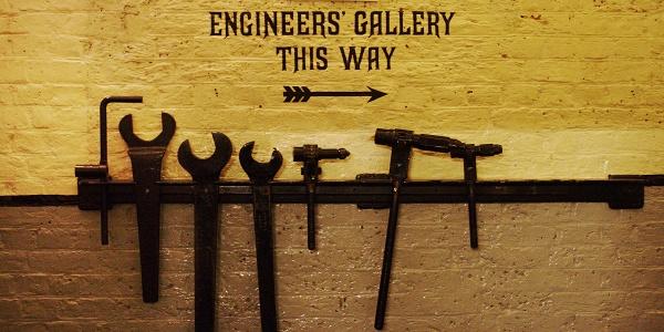 Werkzeug an der Wand, ein Wegweiser zeigt zur Engineers' Gallery