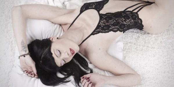 Die schöne Mia räkelt sich in Dessous auf dem Bett