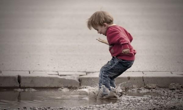 Junge springt in eine Pfütze