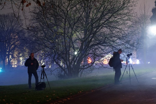 Workshop-Teilnehmer in Aktion zwischen Lampen und Nebel beim nächtlichen Fotokurs zum Winterleuchten im Westfalenpark