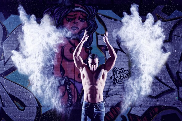 Ein athletischer Mann wirft puderiges Mehl mit den Armen nach oben. Im Bild wirkt das Mehl auf beiden Seiten wie Flügel.
