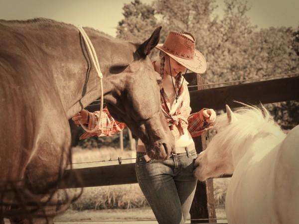 Portrait outdoor: Die schöne Beatrice mit ihrem Pferd und ihrem Pony. Das Pony knabbert an ihrer Hosentasche