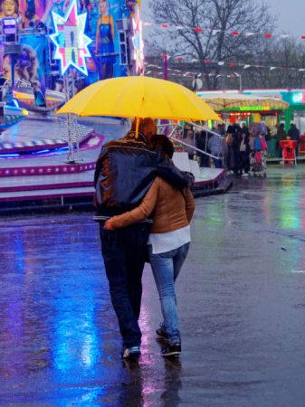 Ein Pärchen unterm gelben Regenschirm auf der Kirmes