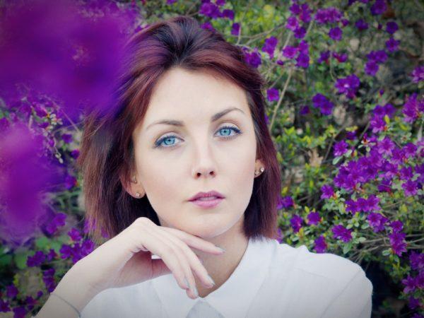 Eine junge Frau sitzt zwischen Blüten