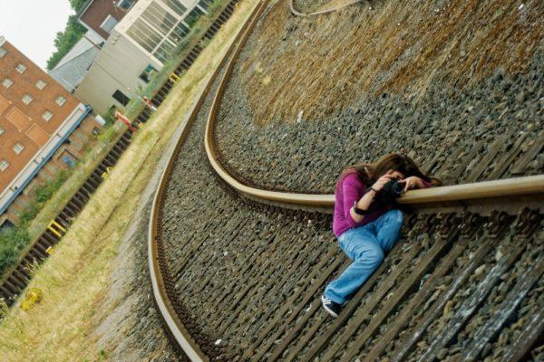 Junge Frau sucht extreme Perspektiven auf einem Gleis