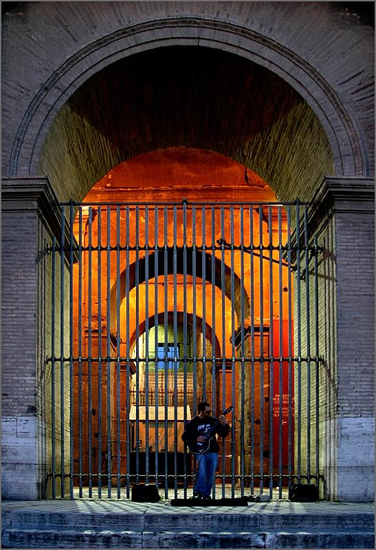Ein Straßenmusiker mit seiner E-Gitarre vor einem der Bögen des Kolosseums. Die Lichtstimmung ist kühl, innerhalb der Bögen scheint warmes Licht.