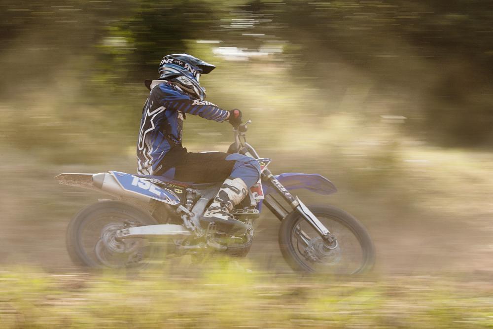Ein Motocross-Fahrer wischt durchs Bild. Die Aufnahme wurde mitgezogen, das heißt das Motorrad ist scharf, der Vorder- und Hintergrund nicht.