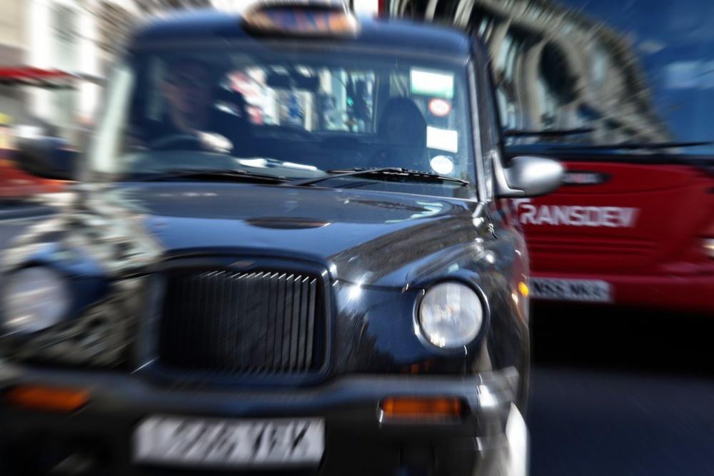Zoom-Aufnahme eines London Taxis mit Bus dahinter. Die Wirkung ist sehr dynamisch direkt auf den Betrachter ausgerichtet.