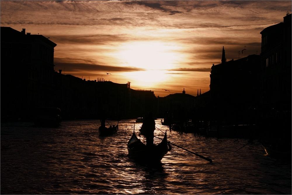 Der Canal Grande bei Sonnenuntergang. Die Sonne spiegelt sich auf dem Wasser. Alle Gebäude und Gondeln sind nur als schwarze Silhouetten zu sehen.