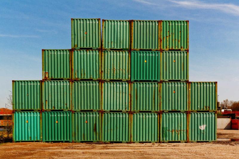 Ein Stapel grüner Überseecontainer auf sandigem Boden