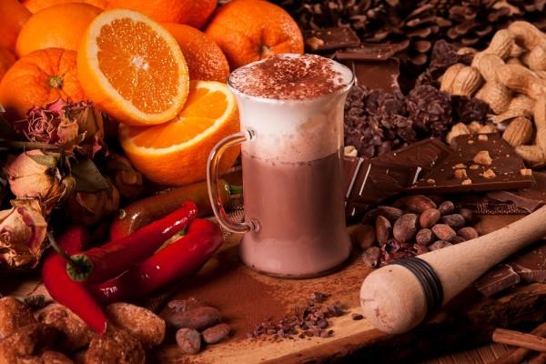 Stilleben mit Kakao, Schokolade, Mutzenmandeln, getrockneten Rosen, Orangen und Nüssen.