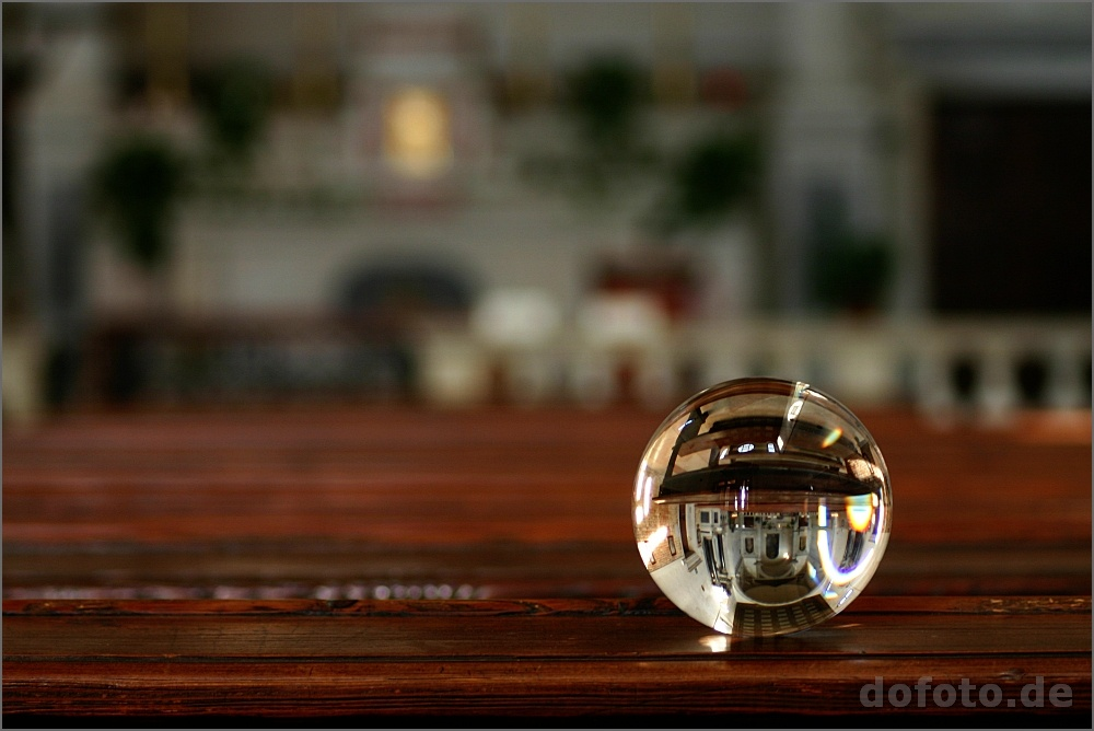Ein Urlaubsfoto von einer Glaskugel auf einer Kirchenbank. In der Kugel ist das ganze Kirchenschiff zu sehen.